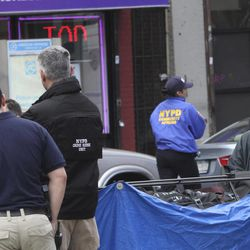 An employee from the coroner's office, right, removes a body from a crime scene in the East Harlem neighborhood of Manhattan, Thursday, April 12, 2012 in New York.  An armed bandit was killed Thursday during a chaotic getaway following a robbery at an East Harlem pharmacy of prescription painkillers and cash, police said.