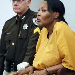 Morris Garner, who also goes by the name Tracey Lynn Garner, waits in a Hinds County courtroom with bailiff Tony Queen, in Jackson, Miss., Tuesday, Sept. 11, 2012, for a bond hearing.  Garner, who dresses and lives as a woman, has been charged with depraved-heart murder after performing an illegal buttocks implant that killed a Georgia woman, authorities said. He is charged with performing the procedure in March at his house in Jackson, Miss. Mississippi Attorney General Jim Hood said during a news conference that Garner had no training or license to perform such a procedure.