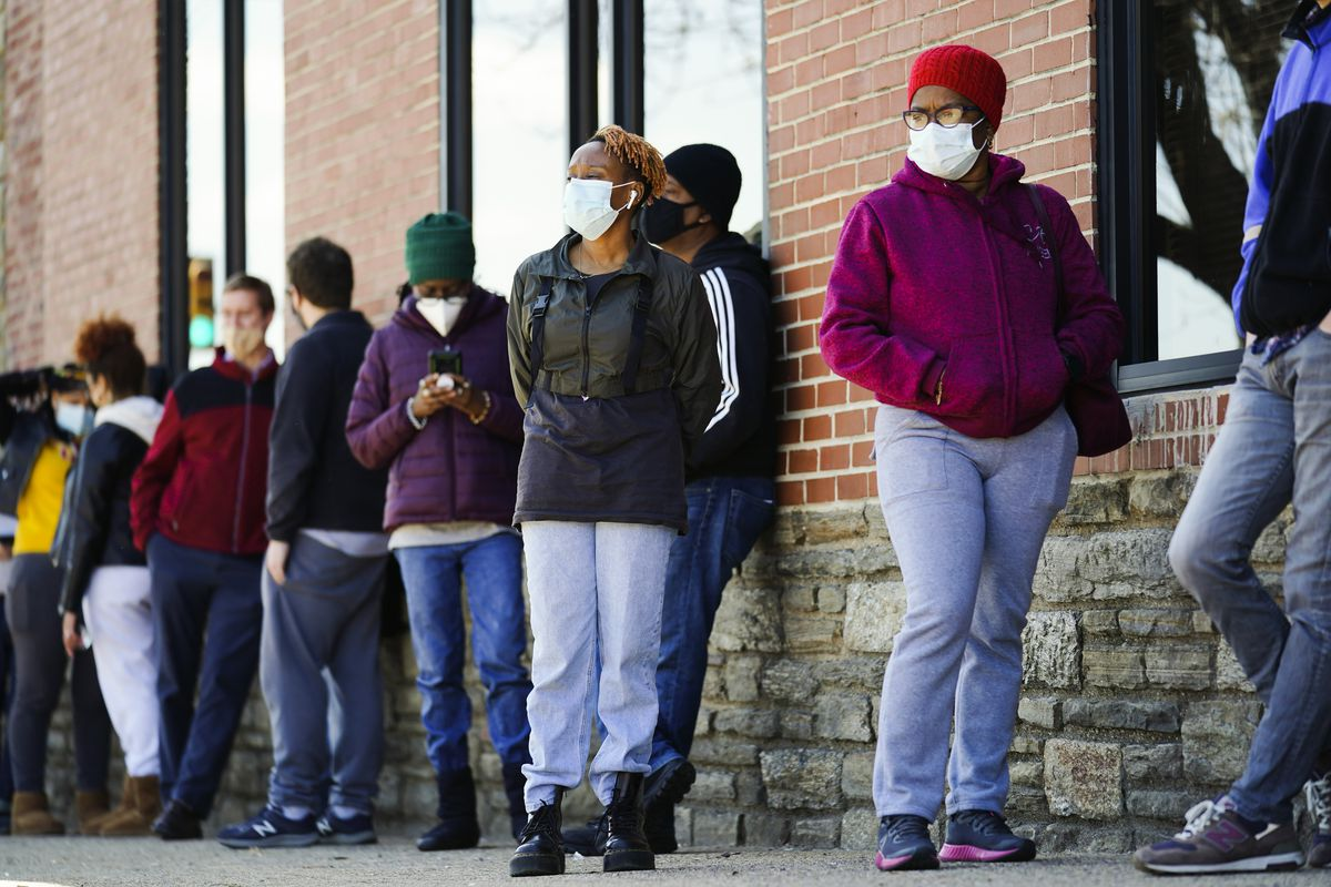 In this March 29, 2021, file photo, people wearing face masks as a precaution against the coronavirus wait in line to receive COVID-19 vaccines at a site in Philadelphia.