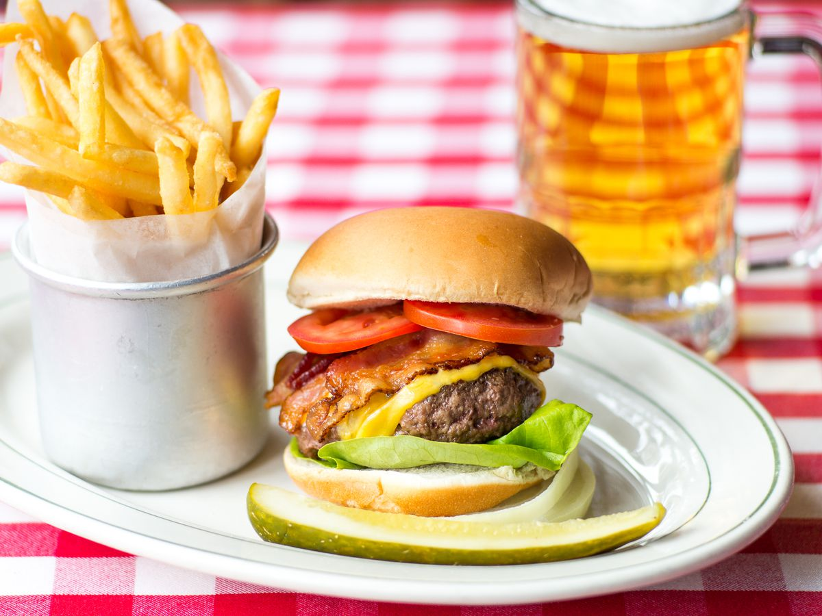 A tall cheeseburger and side of fries sit on a table with a checkered tablecloth