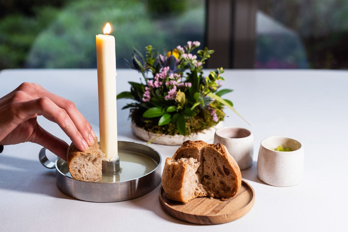 A lit candle made of beef fat in a pewter base, into which bread is dipped
