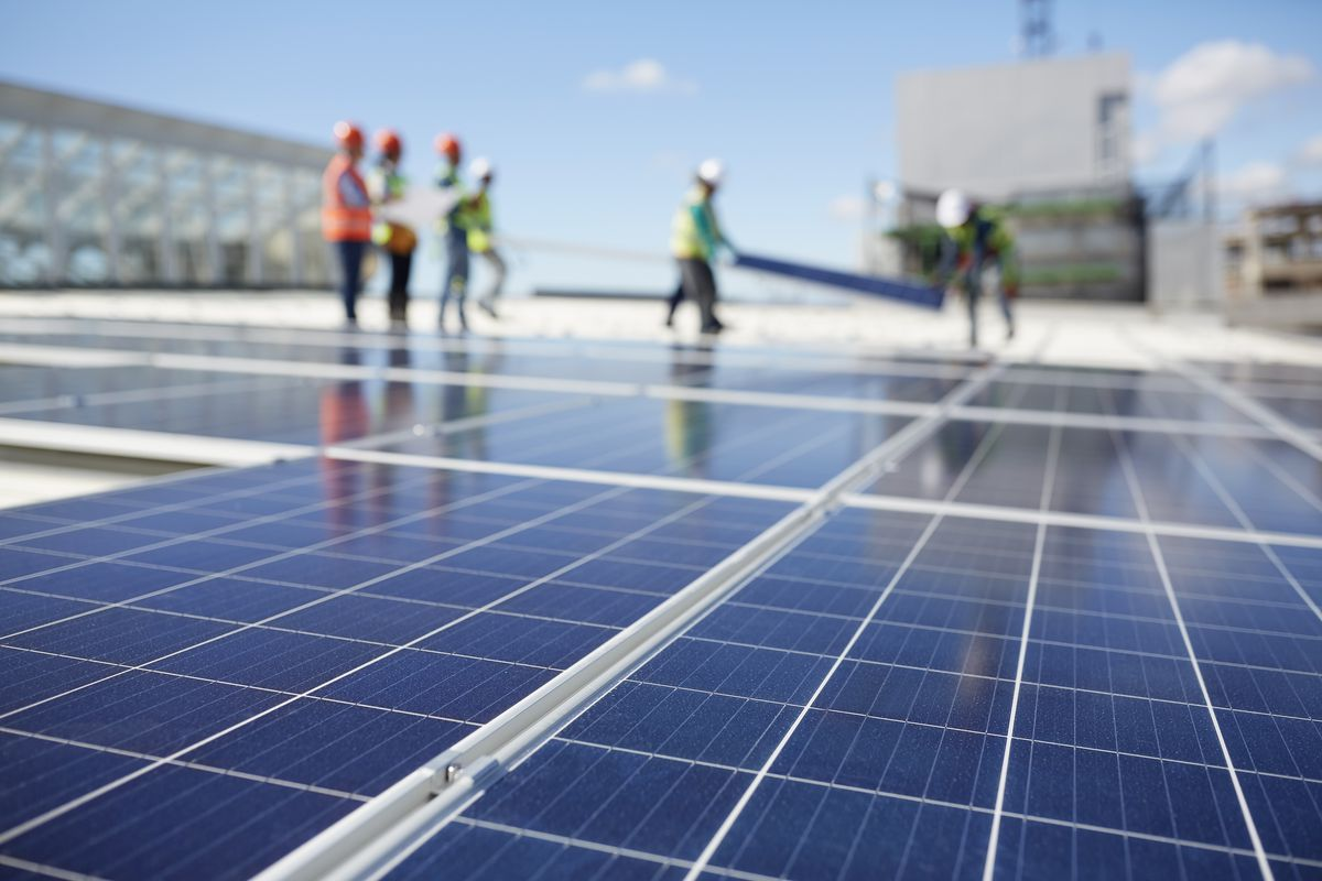A stock photo of several workers installing solar panels on a flat rooftop.
