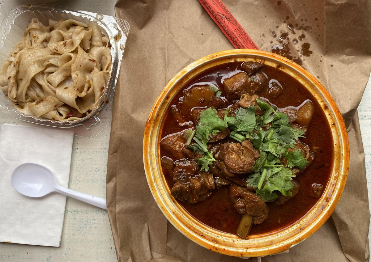 An overhead photograph of a bowl of brick-red soup with chunks of chicken, potatoes, and sprigs of cilantro. A takeout container of noodles sits to the side.