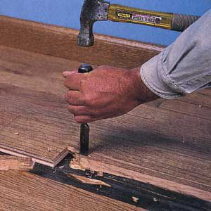 Man Chisels Out Edges Of Old Floorboard