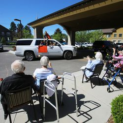 Families wave and cheer as they drive past residents at The Ridge Cottonwood senior living center in Holladay for Mother's Day on Saturday, May 9, 2020.