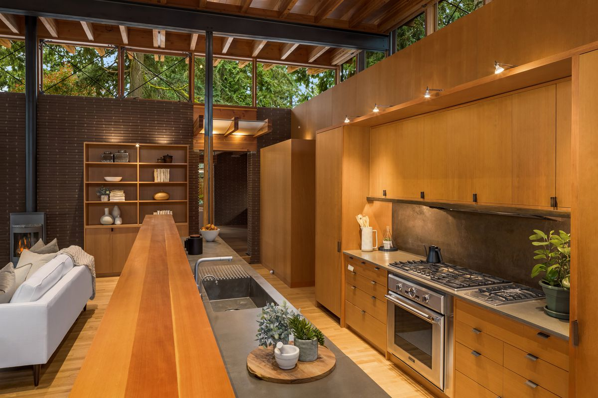 A kitchen area with wood cabinets, dark counters, and views to living room.
