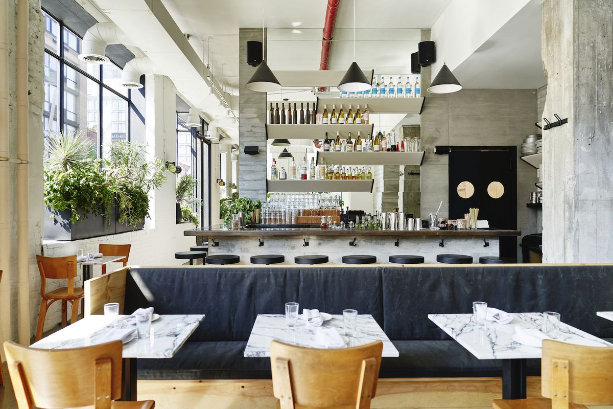 The interiors of a restaurant space with light brown chairs up front, small marble tables, a blue banquette, and a bar in the background.
