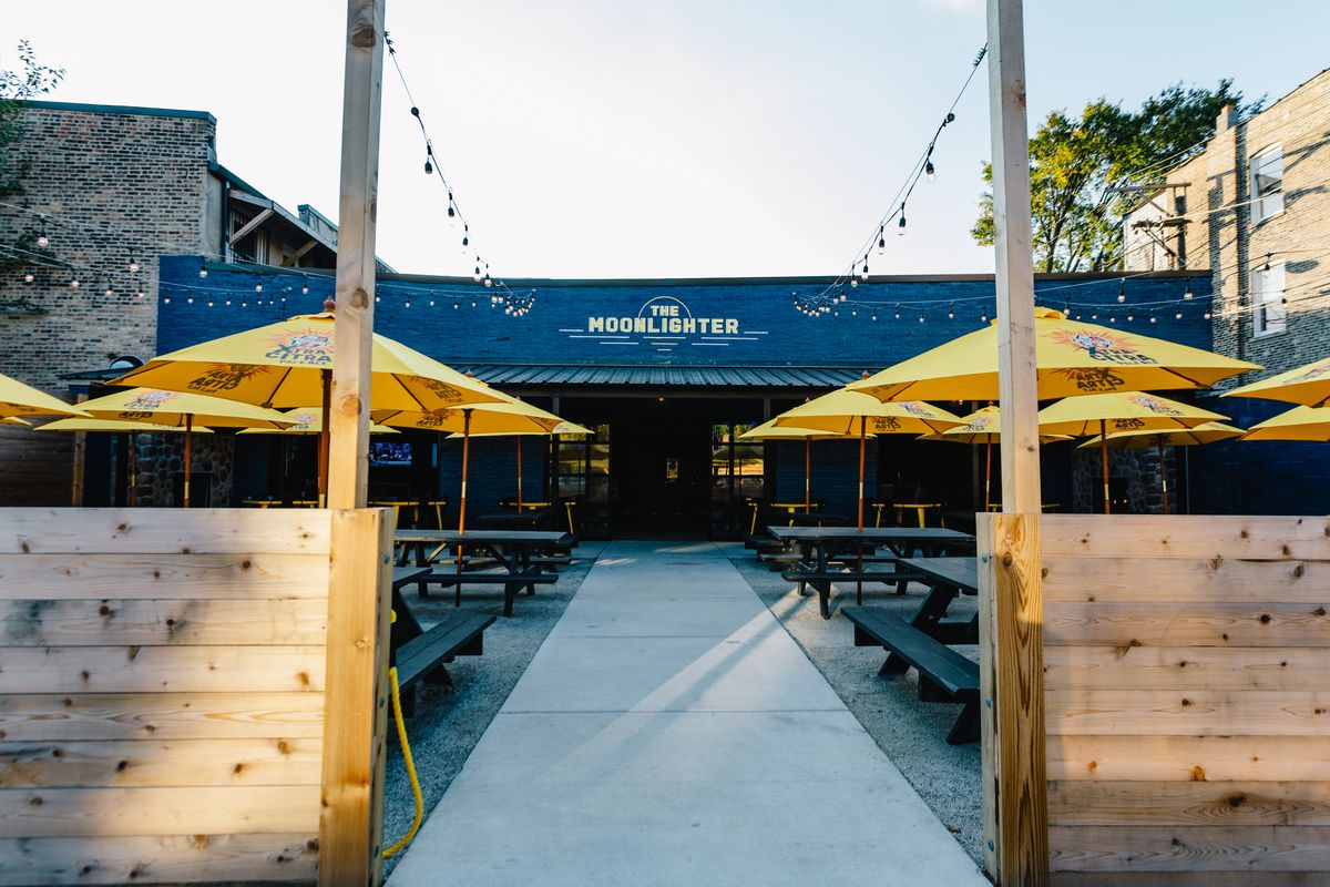 """A blue building sits far back with the words """"the Moonlighter"""" written in yellow. In front, there is a large patio with yellow umbrellas over black tables. Two short wooden walls separate the patio from the sidewalk."""