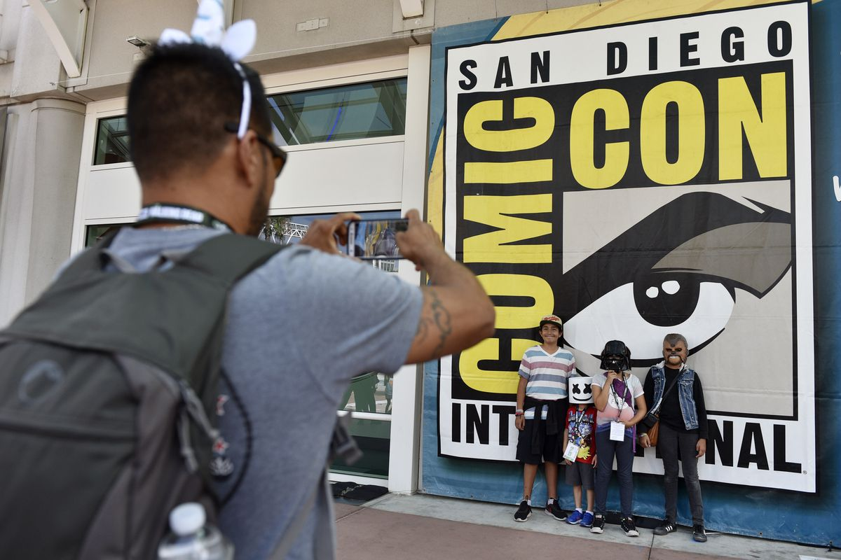 FILE - Luis Ramos, left, of San Diego takes a picture of his son Alek, 6, third from right, and daughter Anabel, 11, second from right, and their friends Emiliano Beltran, 12, fourth from right, and Isabel Beltran, 10, before Preview Night at the 2018 Com