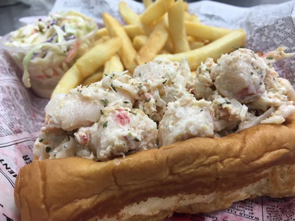 A lobster roll with French fries and coleslaw
