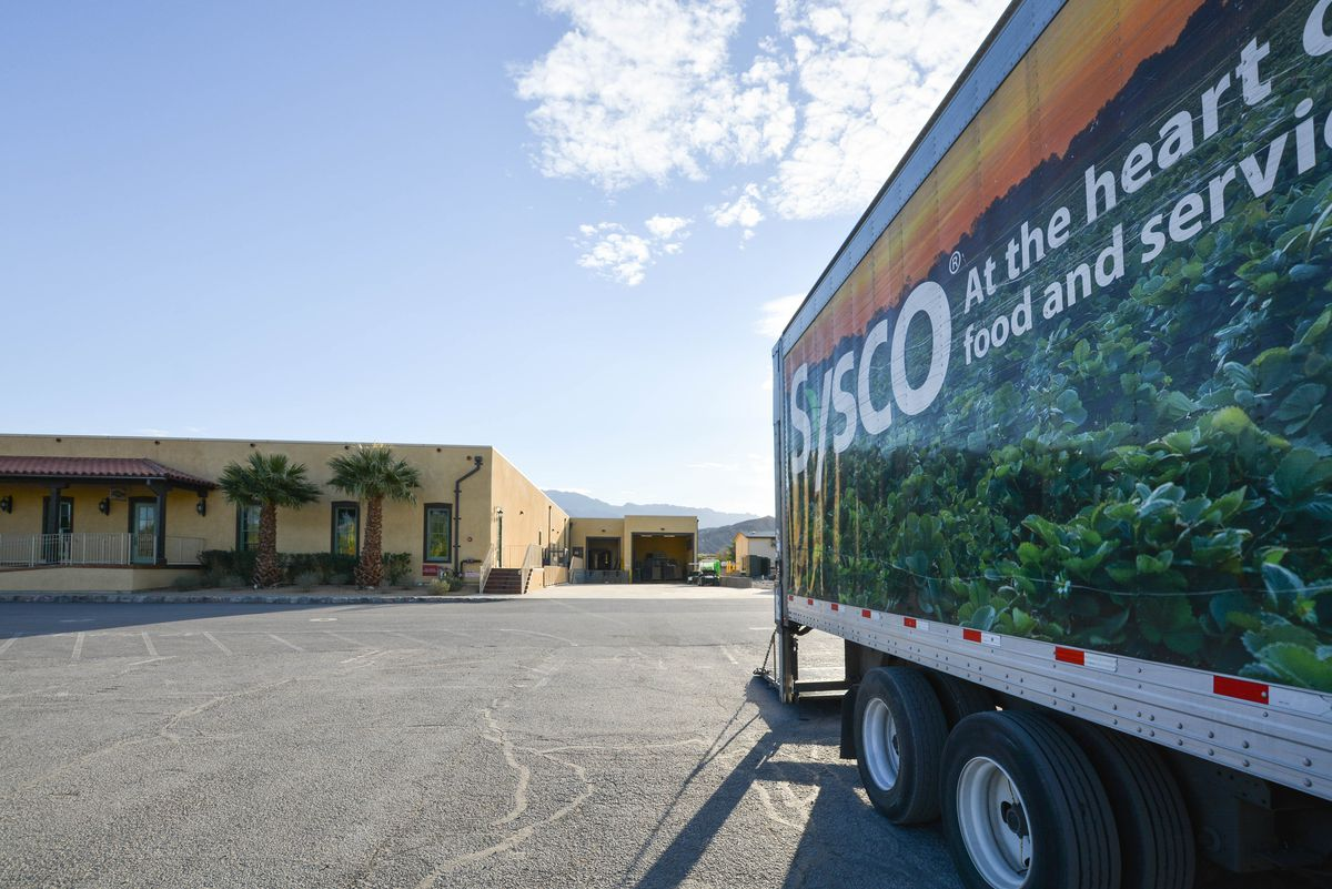 A large truck holding food drives into a desert oasis property.