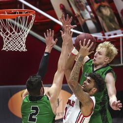 Utah Utes forward Timmy Allen (1) fights past UVU Wolverines forward Evan Cole (2) and UVU forward Tim Fuller (5) for a basket during a game at the Huntsman Center in Salt Lake City on Tuesday, Dec. 15, 2020.