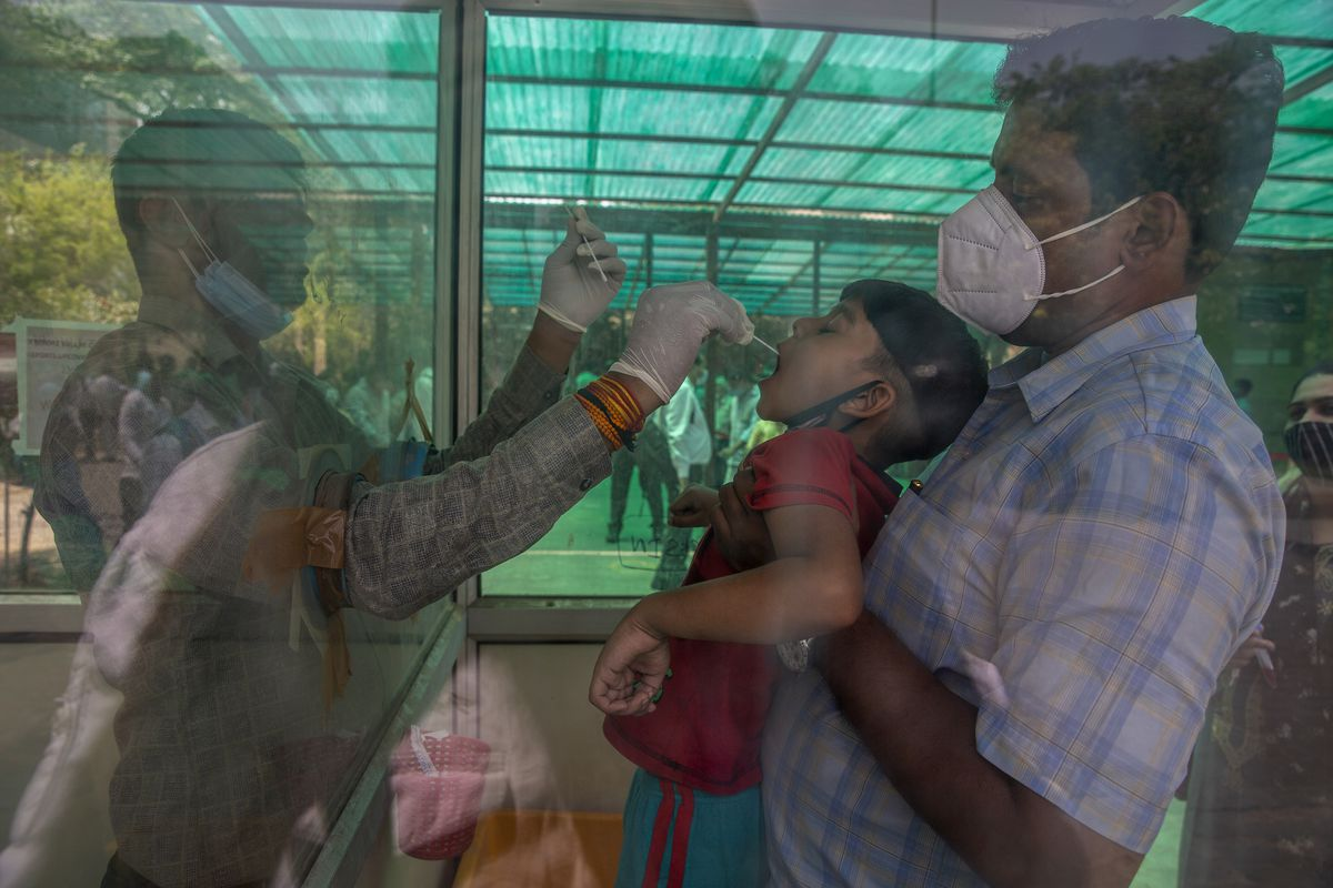 A health worker takes a swab sample of a child to test for COVID-19 at a government hospital in Noida, a suburb of New Delhi, India, Thursday, April 15, 2021. India reported more than 200,000 new coronavirus cases Thursday, skyrocketing past 14 million overall as an intensifying outbreak puts a grim weight on its fragile health care system.