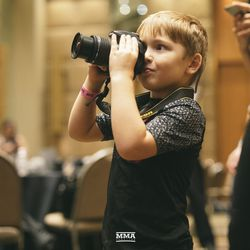 Sam Alvey's son takes a photo at UFC 234 media day.