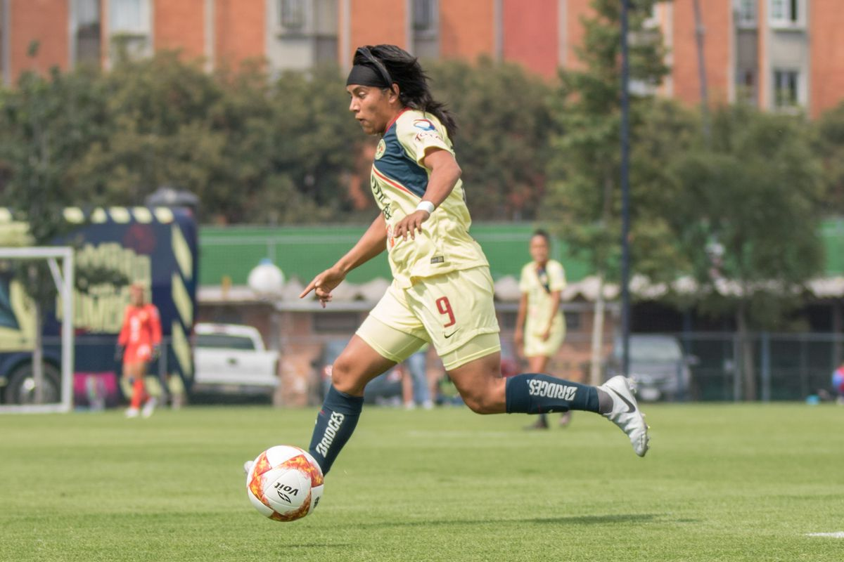 Lucero Cuevas dribbles the ball for Club América Femenil against Pumas Femenil.
