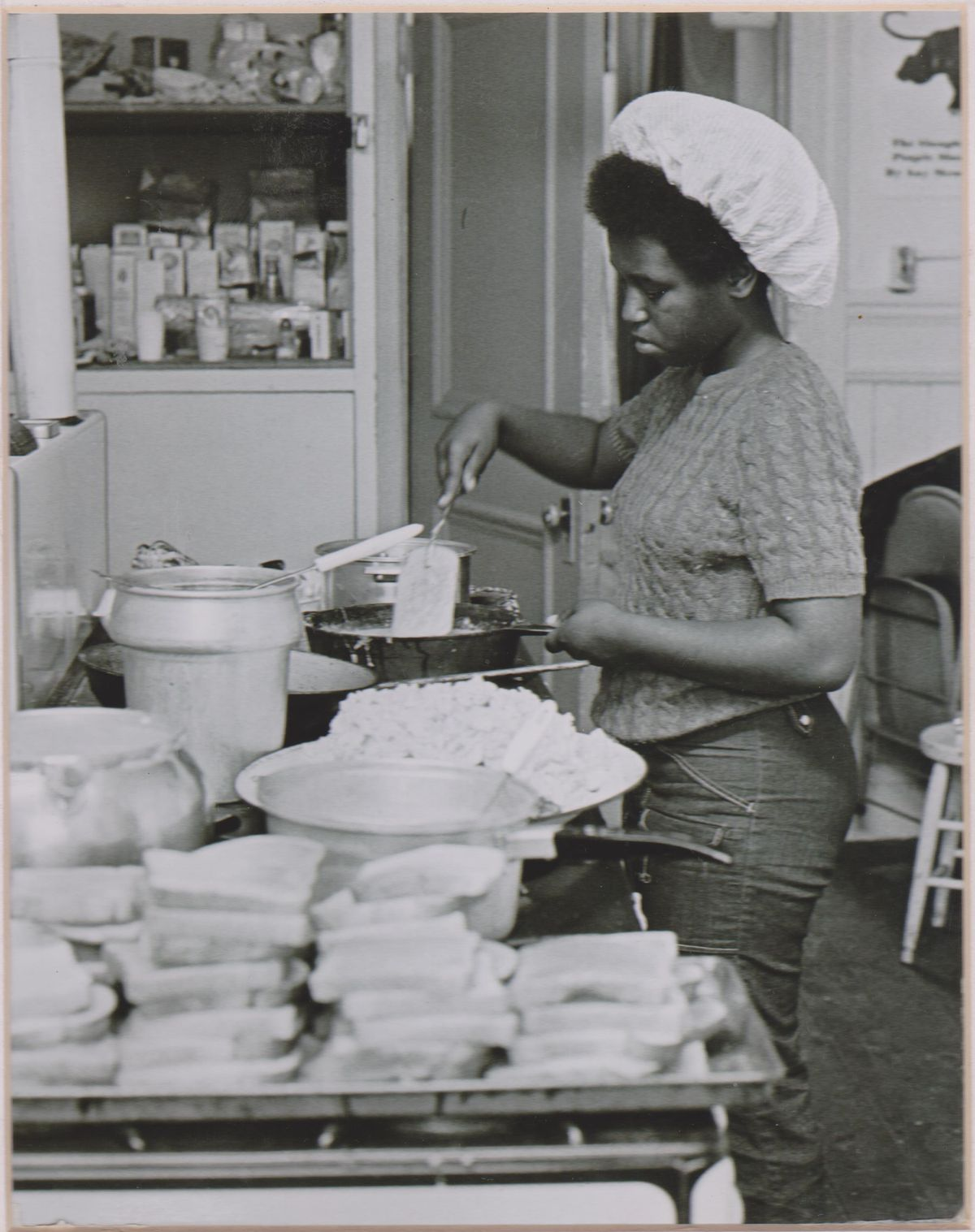 A cook wearing a hairnet stands in a kitchen preparing meals for school children.