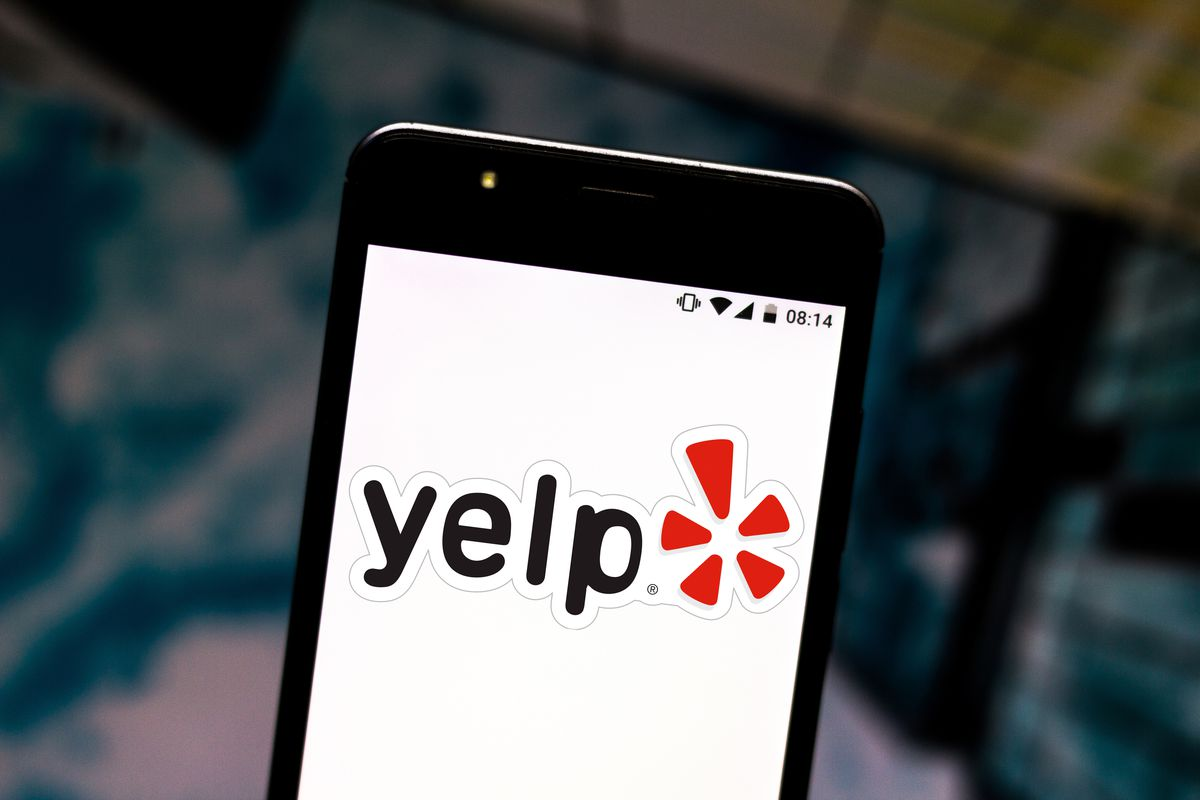 In this photo illustration the Yelp logo is seen displayed...