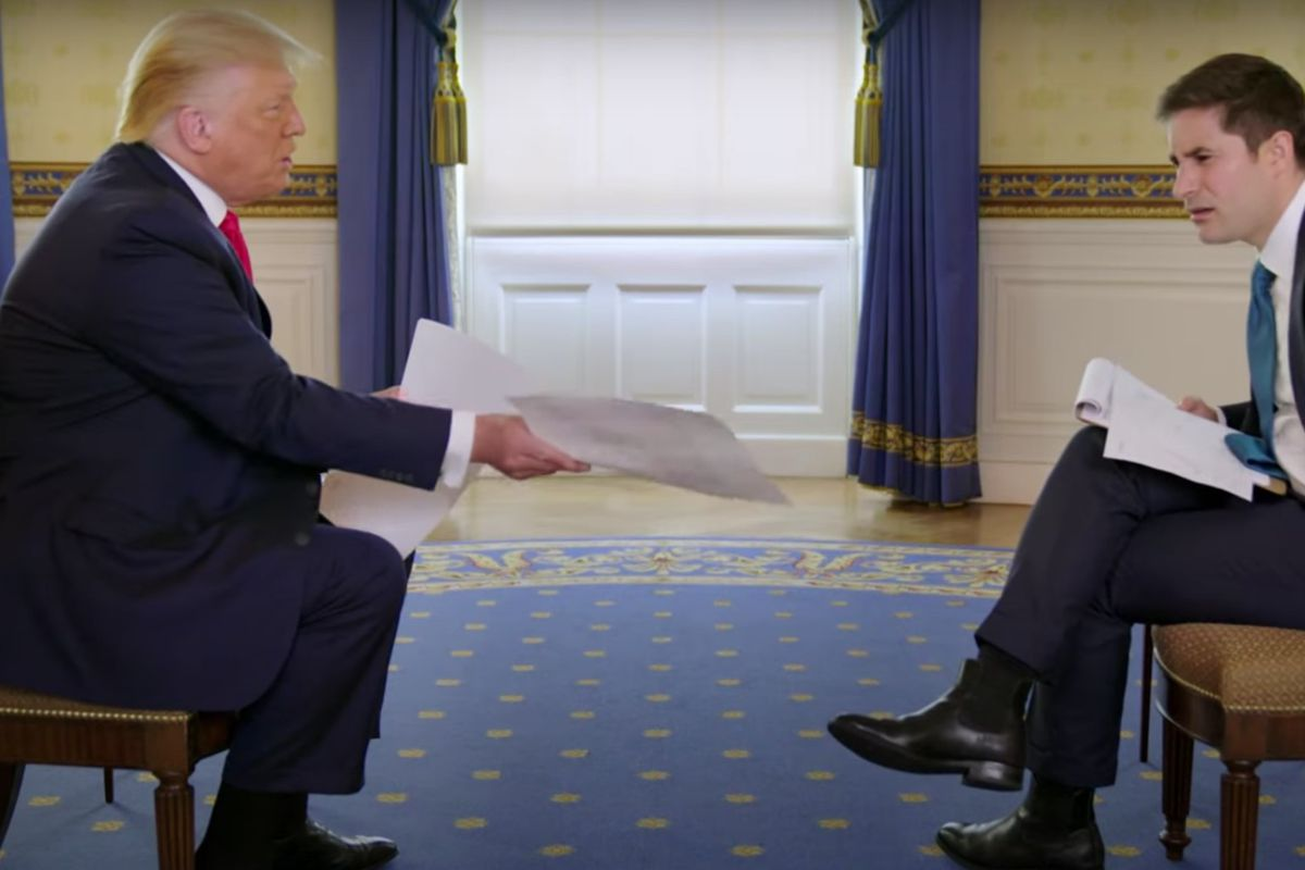 President Trump sitting across from his interviewer and showing him a piece of paper.