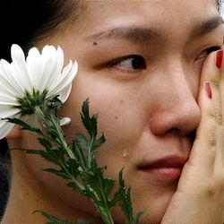 A South Korean woman wipes tears as she holds a flower for the late former South Korean President Kim Dae-Jung during a memorial service at Seoul Plaza in Seoul, South Korea, Wednesday.