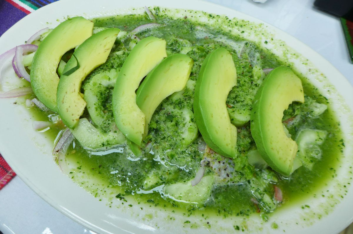A very soupy green plate with sliced avocados on top.