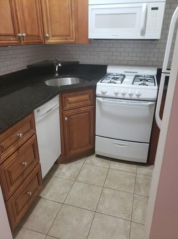 A small kitchen with a stove at the end of an L-shaped counter.