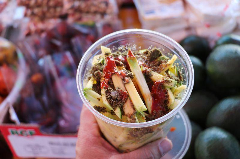 Loaded green mango snack with lime juice, salt, and ground pumpkin seeds at Koreatown's Salvadoran street market.