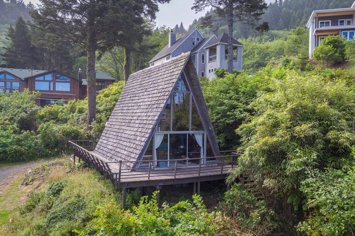 An A-frame house with a wall of windows and a deck surrounding it sits in a green lot.