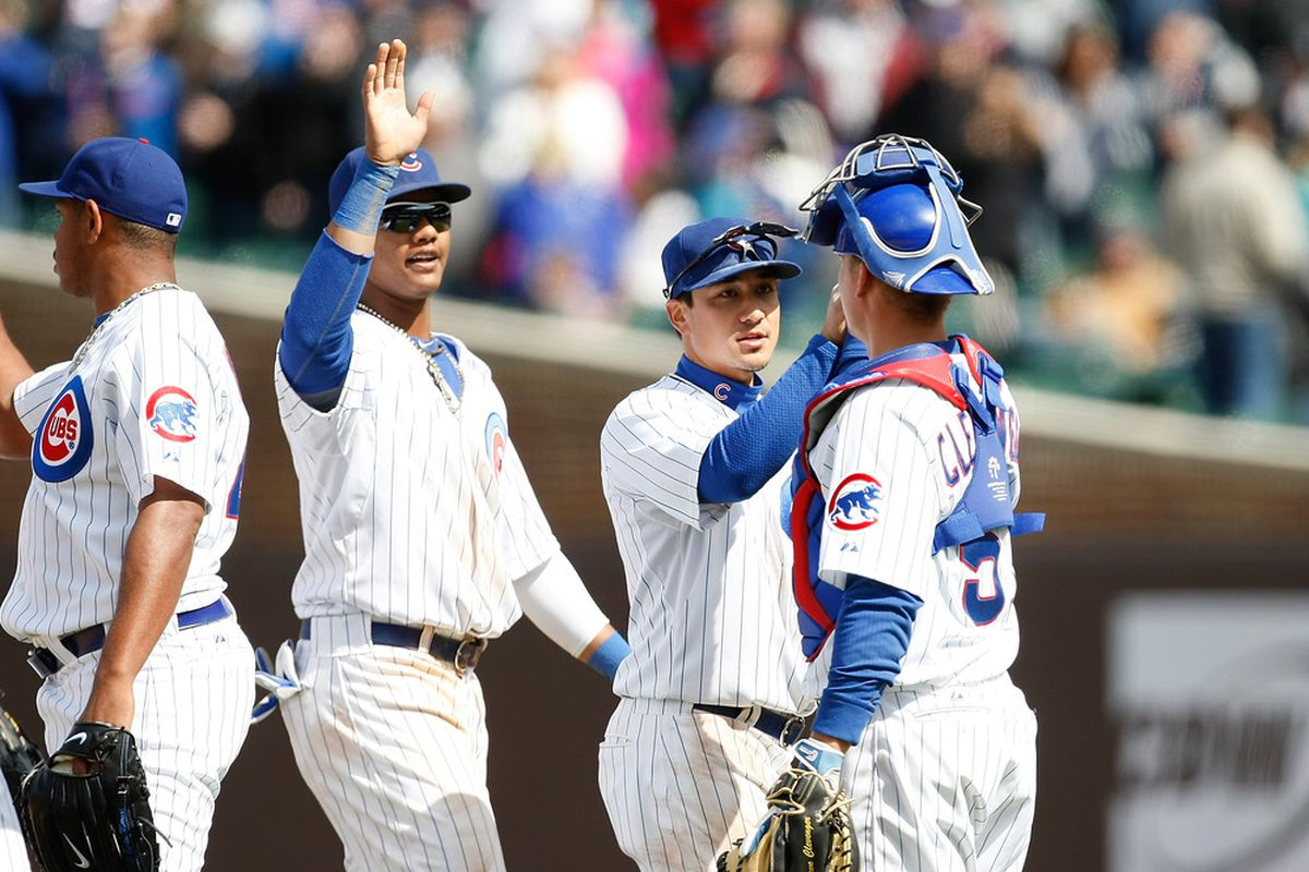 Steve Clevenger of the Chicago Cubs congratulates Darwin Barney and Starlin Castro after the win against the Cincinnati Reds at Wrigley Field in Chicago, Illinois. The Cubs defeated the Reds 6-1. (Photo by Scott Boehm/Getty Images)