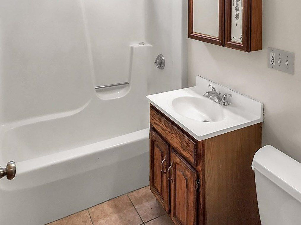 A small bathroom with no curtain on the tub.