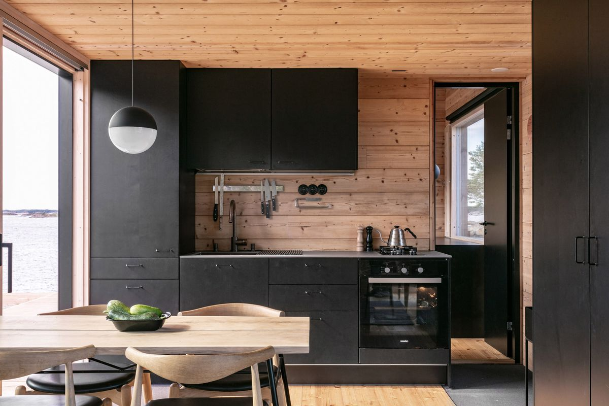 Kitchen with black cabinets and pale wood dining table, chairs, and walls.