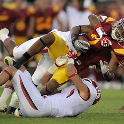 FILE - In this Sept. 10, 2011, file photo, Southern California wide receiver Robert Woods is taken down by Utah defensive back Reggie Topps, top, and linebacker Brian Blechen during an NCAA college football game in Los Angeles. Woods, the 18th-ranked Trojans' top receiver, missed practice Wednesday, Nov. 16, 2011, to rest an accumulation of injuries, and coach Lane Kiffin thinks the problems with Woods' ankle and shoulder might keep him out of USC's upcoming visit to No. 4 Oregon. (AP Photo/Mark J. Terrill, File)