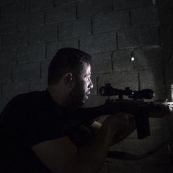 Free Syrian Army fighter scans for targets from a building in Aleppo, Syria, Thursday, Sept. 27, 2012.