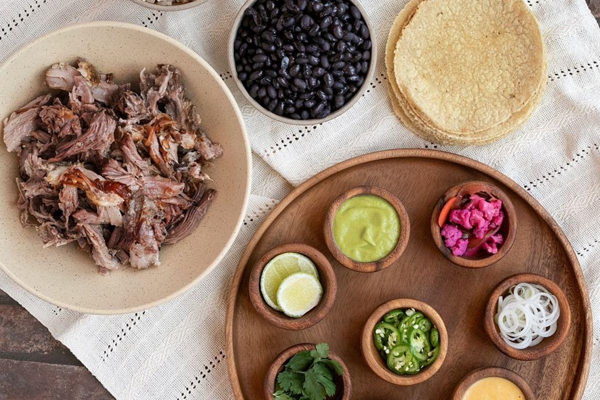 A carnitas spread with a big bowl of crusty meat, a bowl of black beans, a stack of white corn tortillas, and a wooden tray with a variety of condiments like sliced jalapeños, pickled onions, and salsas