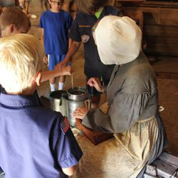 A Boy Scout troupe learns how to make candles with a descendent of John Rowe Moyle at Moyle Park in July 2014. The park's pioneer activities every Tuesday are a popular event for Boy Scouts and other church youth groups.