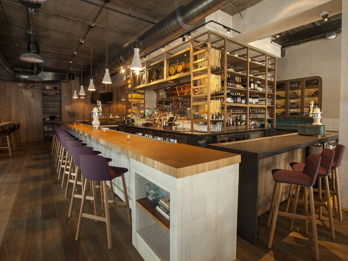 A simple, sleek bar with backed stools and a rack for pasta.