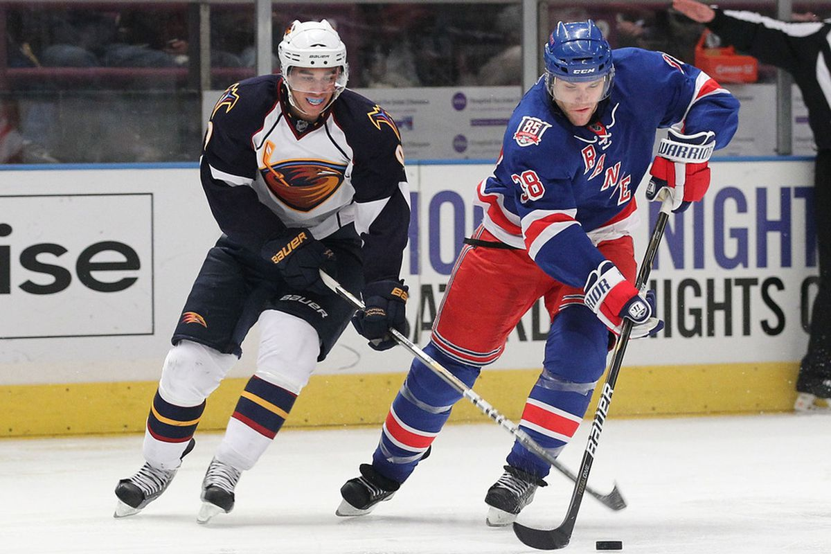 Michael Sauer (38) of the New York Rangers skates with the puck as Evander Kane (9) of the Atlanta Thrashers defends during their game on April 7, 2011 at Madison Square Garden in New York City, New York.  (Photo by Al Bello/Getty Images)