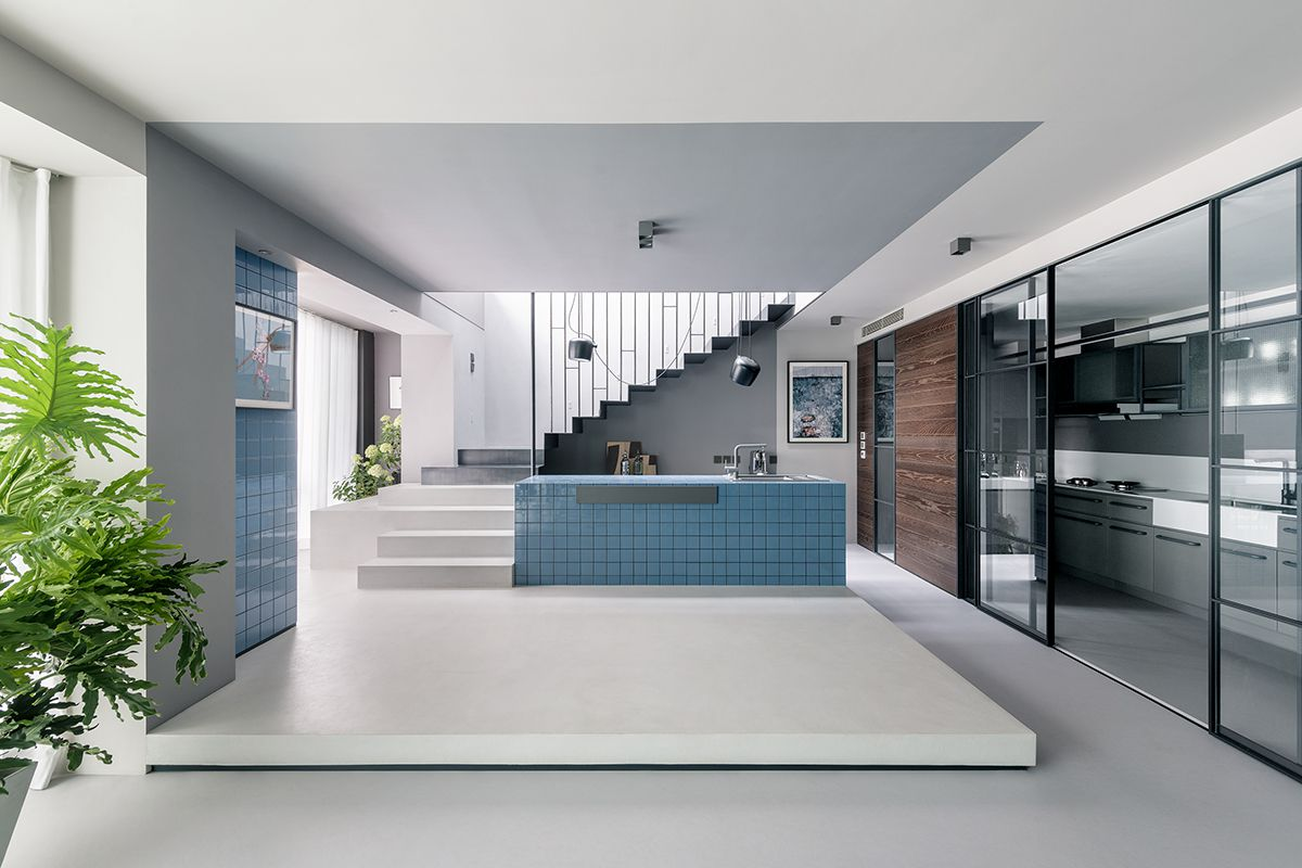 A kitchen island clad in blue tiles stands in the center of an open space. Black and gray stairs are in the background, while sliding glass doors open on the right into more kitchen space.
