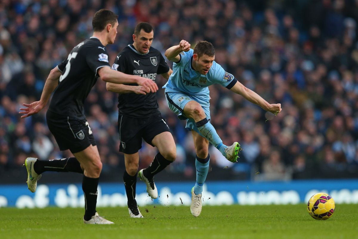 James Milner of Manchester City passes the ball past Michael Keane of Burnley during the Barclays Premier League match between Manchester City and Burnley at Etihad Stadium on December 28, 2014 in Manchester, England.