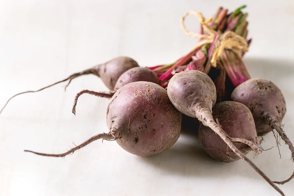 Bundle of young organic garden beetroot over white marble background.