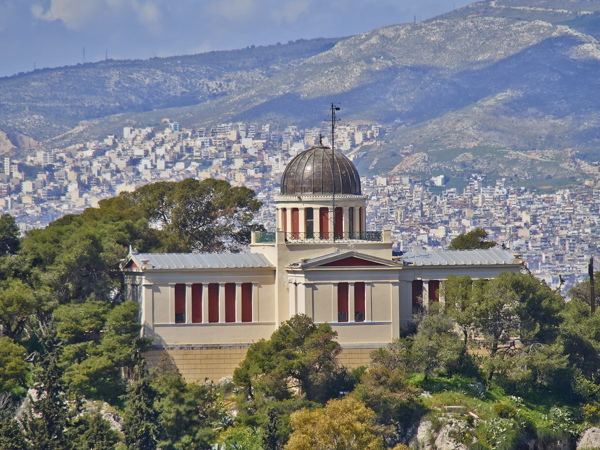 An aerial view of the National Observatory of Athens. The observatory has a domed roof and multiple windows. It is situated on a mountain overlooking the city of Athens.