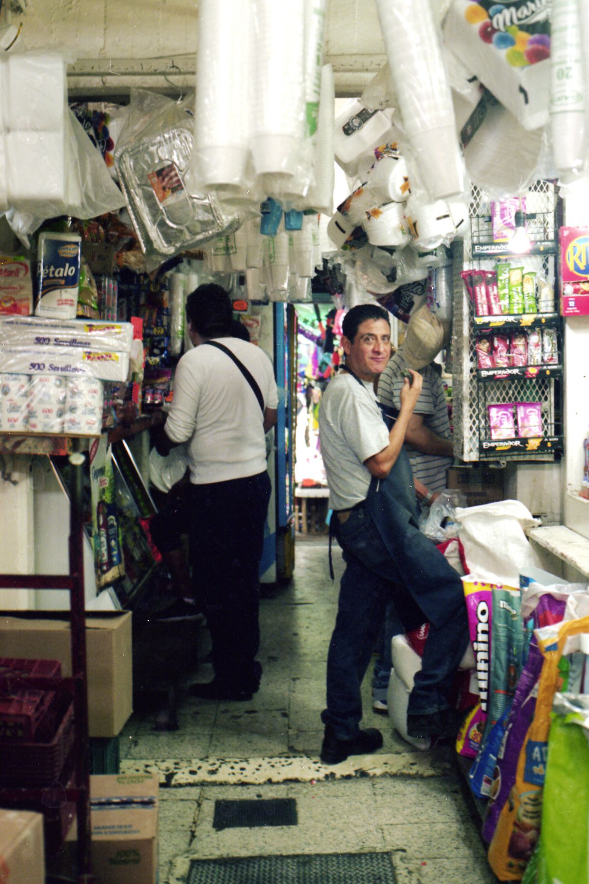 A vendor looks at the camera in his stall selling household goods