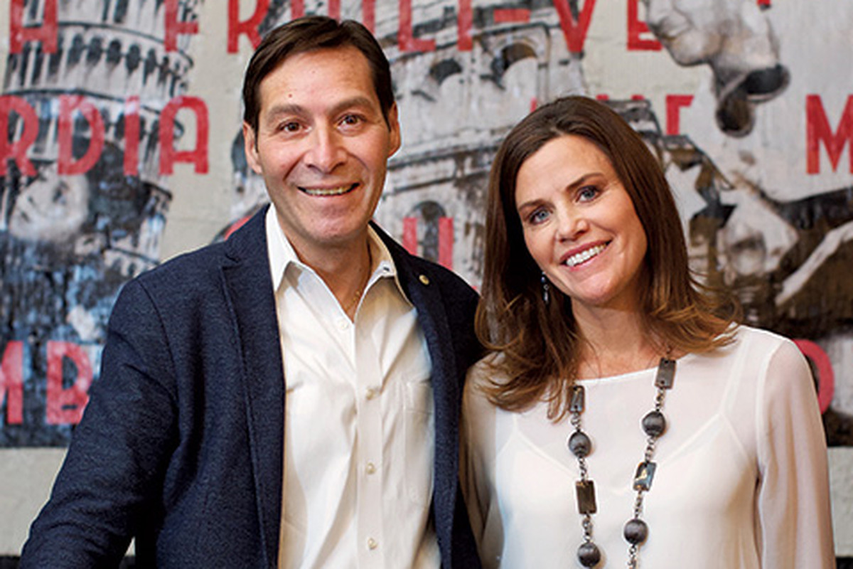 A photo of I'm Eddie Cano's owners Massimo and Carolyn Papetti posing in their chic upper Northwest restaurant.