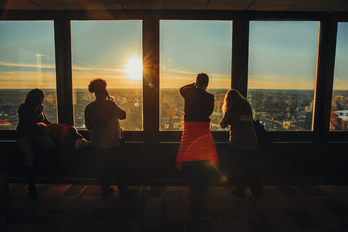 People looking out of and photographing from a high observation deck in a skyscraper.