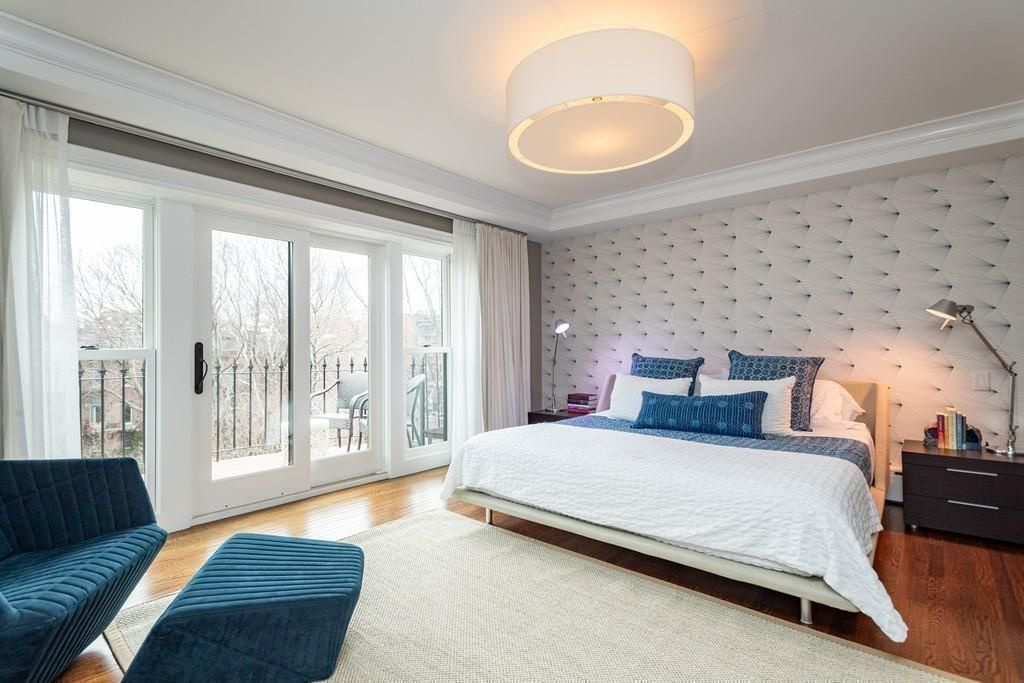 An airy bedroom with a large bed and floor-to-ceiling glass doors.
