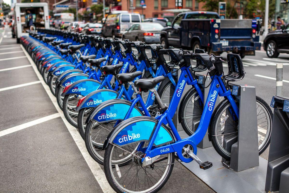 A row of bright-blue Citi Bikes docked at a bike dock.