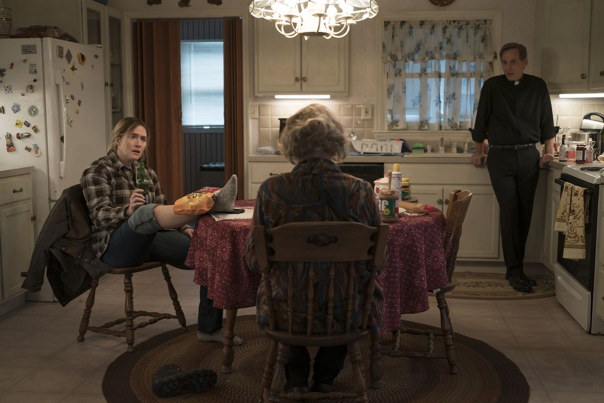 a group of three people including kate winslet on the show mare of easttown with mare icing her leg with french fries and drinking a rolling rock