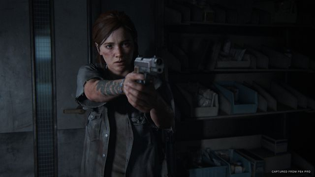 Ellie in The Last of Us 2 pointing a gun toward the camera.