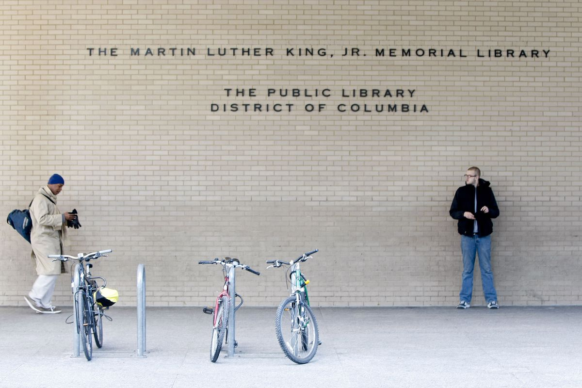 The brick facade of the Martin Luther King Jr. Library up close, with two men standing out front.