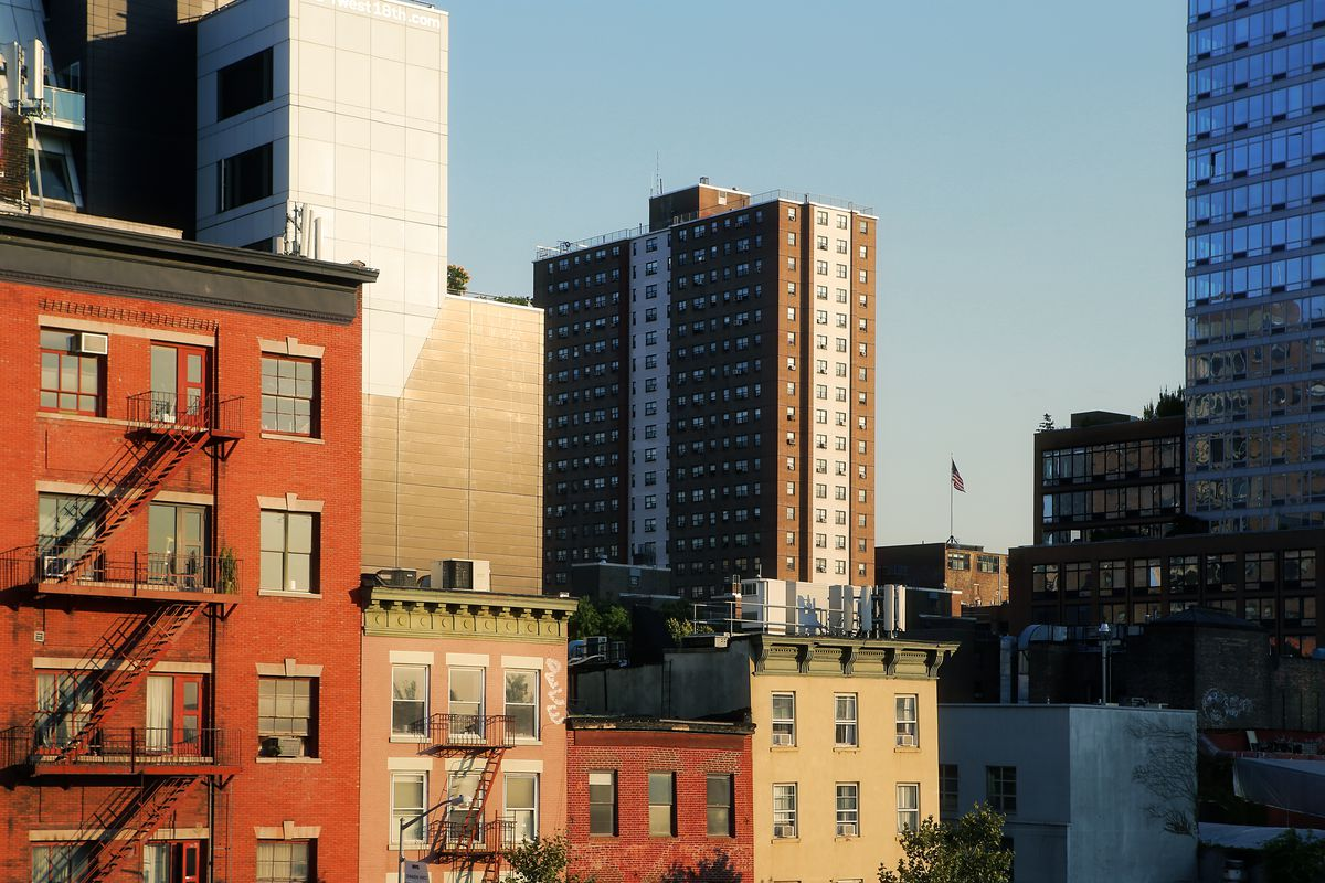 A brown public housing building rises among different residential buildings in New York City.