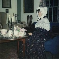 Susan Evans McCloud in one of Tasha Tudor's gowns in her Best Parlor by the light of 20 candles in 1989.